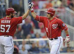 Washington Nationals' Wilson Ramos, right, gets high five from Tanner Roark (57) after Ramos hit a home run during the second inning of a baseball game against the Baltimore Orioles, Monday, Aug. 4, 2014, in Washington. (AP Photo/Nick Wass)