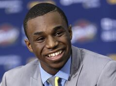 FILE - In this June 27, 2014, file photo, Cleveland Cavaliers draft pick Andrew Wiggins smiles during an NBA basketball conference in Independence, Ohio. Two people with knowledge of the deal tell The Associated Press that Minnesota and Cleveland have agreed to a trade that will send All-Star forward Kevin Love to the Cavaliers for Wiggins, Anthony Bennett and a future first-round draft pick. The two people spoke Thursday, Aug. 7, 2014, on condition of anonymity because no official agreement can be reached until Aug. 23, when Wiggins, this year's No. 1 draft pick, becomes eligible to be traded. (AP Photo/Tony Dejak, File)