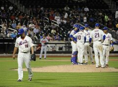 New York Mets relief pitcher Daisuke Matsuzaka (16) walks to the dugout after manager Terry Collins (10) took him out of the baseball game after he gave up three runs to the Atlanta Braves in the ninth inning at Citi Field on Thursday, Aug. 28, 2014, in New York. The Braves won 6-1.(AP Photo/Kathy Kmonicek)