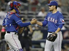 Texas Rangers catcher Robinson Chirinos (61) congratulates Rangers relief pitcher Joakim Soria (28) after Soria closed out the Rangers 4-2 defeat of the New York Yankees in a baseball game at Yankee Stadium in New York, Monday, July 21, 2014. (AP Photo/Kathy Willens)