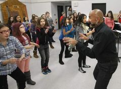 Teacher Gerald Bohemier rehearses Edmund Partridge School students in a munchkins scene from The Wizard of Oz.