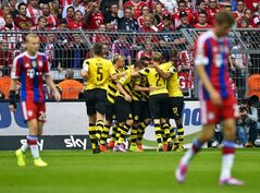 Dortmund's players celebrate their opening goal by Henrikh Mkhitaryan during the German soccer Super Cup match between Borussia Dortmund and Bayern Munich in Dortmund, Germany, Wednesday, Aug. 13, 2014. (AP Photo/Sascha Schuermann)