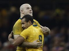 FILE - In this Nov. 30, 2013 file photo, Australia's Stephen Moore, left, and Will Genia celebrate their win against Wales at the end of their autumn international rugby match at Millennium Stadium in Cardiff, Wales. Hooker and 91-test veteran Moore has been named Wallabies captain for this month's test series against France and the important lead-up to next year's Rugby World Cup. (AP Photo/Sang Tan, File)