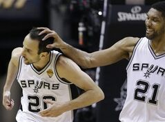After dunking against the Miami Heat, San Antonio Spurs guard Manu Ginobili (20) is congratulated by forward Tim Duncan (21) during the first half in Game 5 of the NBA basketball finals on Sunday, June 15, 2014, in San Antonio. (AP Photo/David J. Phillip)