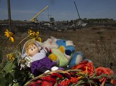 Toys and flowers are placed at the crash site of Malaysia Airlines Flight 17 near the village of Hrabove, eastern Ukraine, Donetsk region, eastern Ukraine Monday, July 21, 2014. Another 21 bodies have been found in the sprawling fields of east Ukraine where Malaysia Airlines Flight 17 was downed last week, killing all 298 people aboard. (AP Photo/Dmitry Lovetsky)