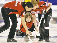Switzerland�s Carmen Kung, Mirjam Ott and Janine Greiner, left to right, move a stone as they play Sweden in the gold medal game at the Ford World Women�s Curling Championships in Lethbridge, Alta. on Sunday, March 25, 2012. THE CANADIAN PRESS/Andrew Vaughan