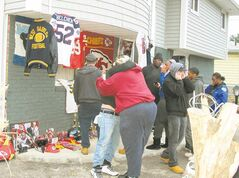 Friends and relatives of Kansas City Chiefs linebacker Jovan Belcher (inset) grieve outside the player's home in West Babylon, N.Y. Saturday.