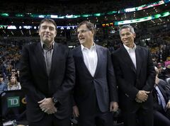 FILE - In this Dec. 18, 2013, file photo Boston Celtics managing partner Wyc Grousbeck, left, stands with venture capitalist Bob Higgins, center, and team co-owner Mark Wan, right, stand during a break in the action at an NBA basketball game in Boston. The three men, investors at Causeway Media Partners, have invested in Street League Skateboarding, a professional circuit for the growing sport. (AP Photo/Elise Amendola, File)