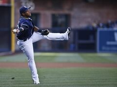 San Diego Padres third baseman Yangervis Solarte makes the off balance throw to get Los Angeles Dodgers' Dee Gordon at first after Gordon bunted in the first inning of a baseball game Saturday, Aug. 30, 2014, in San Diego. (AP Photo/Lenny Ignelzi)