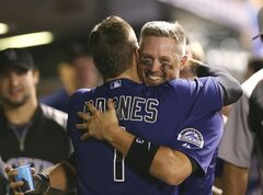 Colorado Rockies' Brandon Barnes, front, hugs teammate Michael Cuddyer after he scored on a single hit by pinch-hitter Drew Stubbs against the Cincinnati Reds in the eighth inning of the Rockies' 10-5 victory in a baseball game in Denver on Sunday, Aug. 17, 2014. The game is being made up after it was postponed on Saturday by a water main break that left the stadium waterless. (AP Photo/David Zalubowski)
