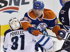 Winnipeg Jets' goalie Ondrej Pavelec (31) is elbowed by Edmonton Oilers' Nail Yakupov (64) during second period NHL hockey action in Edmonton, Alta., on Monday.