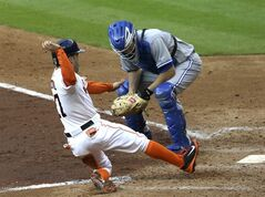 Houston Astros' Jose Altuve (27) slides to score next to Toronto Blue Jays catcher Josh Thole during the fifth inning of a baseball game Saturday, Aug. 2, 2014, in Houston. Altuve scored from first base on throwing errors by starting pitcher R.A. Dickey and first baseman Danny Valencia. (AP Photo/Pat Sullivan)