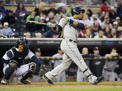 Seattle Mariners' Robinson Cano watches his RBI double in front of Minnesota Twins catcher Kurt Suzuki (8) during the fifth inning of a baseball game in Minneapolis, Friday, May, 16, 2014. (AP Photo/Craig Lassig)