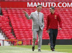 Manchester United's new player Angel Di Maria, right, and manager Louis van Gaal, pose for photographers, at Old Trafford Stadium in Manchester, England, Thursday, Aug. 28, 2014. Manchester United have signed winger Angel Di Maria from Real Madrid for a British record transfer fee of �59.7m. The Argentine winger had a medical in Manchester on Tuesday and has signed a five-year deal. (AP Photo/Alastair Grant)