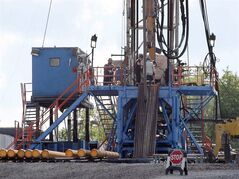 In this June 25, 2012 photo, a crew works on a gas drilling rig at a well site for shale based natural gas in Zelienople, Pa. THE CANADIAN PRESS/AP, Keith Srakocic