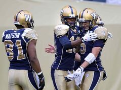 Winnipeg Blue Bombers #19 Aaron Kelly and quarterback Drew Willy celebrate the second of Kelly's TDs in the first quarter Thursday at Investors Group Field in WInnipeg as #81 Cory Watson looks on.