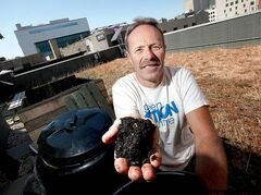 Dave Elmore holds finished compost from the composters atop the Mountain Equipment Co-op building downtown.