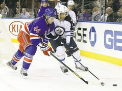New York's Steve Eminger and Winnipeg's Evander Kane fight for control of the puck Tuesday.