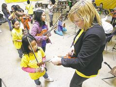 AJ Rosaldo, 8, has her violin tuned by Sistema Winnipeg teacher Barbra Hamilton before Elwick Community School students perform for Winnipeg Harvest volunteers Monday.