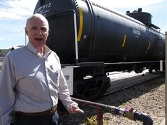 In this April 11, 2014 photo, Grand Canyon Railway train operations general manager Bob Baker poses with the rail cars that are storing water for use on the property in Williams, Ariz. Officials in Williams have declared a water crisis amid a drought that is quickly drying up nearby reservoirs and forcing the community to pump its only two wells to capacity. (AP Photo)