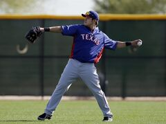 Texas Rangers' Shin-Soo Choo, of South Kore,a throws as he warms up during baseball spring training Tuesday, Feb. 18, 2014, in Surprise, Ariz. (AP Photo/Tony Gutierrez)
