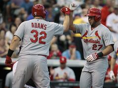 St. Louis Cardinals' Matt Adams (32) congratulates Jhonny Peralta (27) at home plate after Peralta's two-run home run in the fourth inning of a baseball game against the Colorado Rockies in Denver on Tuesday, June 24, 2014. (AP Photo/Joe Mahoney)