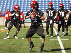 Calgary Stampeders' quarterback Drew Tate, left, takes part in a drill as his teammates look on during the first day of training camp in Calgary, Alta., Sunday, June 1, 2014. The Calgary Stampeders open the regular season Saturday against the Montreal Alouettes feeling less sore and beat up from the pre-season. New turf installed at McMahon Stadium this spring lessened wear and tear on their bodies during training camp. THE CANADIAN PRESS/Jeff McIntosh