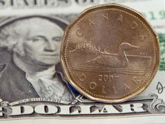 A Canadian dollar, or loonie, sits on top of its American counterpart in Toronto on Sept. 20, 2007. THE CANADIAN PRESS/Adrian Wyld