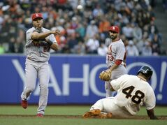 St. Louis Cardinals shortstop Jhonny Peralta, left, turns a double play as San Francisco Giants' Pablo Sandoval, right, is forced out at second base in the second inning of their baseball game Tuesday, July 1, 2014, in San Francisco. The Giants' Michael Morse was out at first base on the play. In the background is Cardinals second baseman Matt Carpenter. (AP Photo/Eric Risberg)
