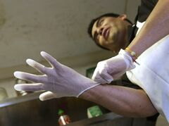 FILE - In this March 12, 2014 file photo, Luis Escamilla puts on gloves before cutting prosciutto at the Hock Farm Restaurant in Sacramento, Calif. California's chefs and bartenders could resume legally handling food with their bare hands under a bill headed to the governor's desk that would repeal an unpopular regulation. The bill, AB2130, passed its final legislative hurdle Thursday, June 26, 2014. with a 32-0 vote in the state Senate. (AP Photo/Rich Pedroncelli,File)