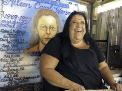 In this May 3, 2012 photo,airbush artist Ted E. Bear sits in front of a portrait she painted of serial killer Aileen Wuronos at The Last Resort Bar in Port Orange, Fla. Almost 22 years after Wuornos was arrested at The Last Resort, the curious still come to the place where she had her last drink. And at the Scoot Inn down the street, it's not unusual for people to walk into the motel office and ask to stay in the same room Wuornos did when she committed a string of murders that left seven men dead. (AP Photo/Brendan Farrington)