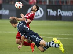 Toronto FC forward Gilberto, back, battles for the ball against Sporting Kansas City defender Matt Besler, front, during first half MLS soccer action in Toronto on Saturday, July 26, 2014. THE CANADIAN PRESS/Nathan Denette