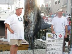 FILE - Citation angler Andy Thomossan, left, and Eric Holmes stand next to their 883-pound blue marlin, which broke the record for the biggest blue marlin in the 52-year history of the Big Rock Blue Marlin Tournament in Morehead City, N.C., in this June 14, 2010 file photo. The boat's owners landed in a fight for the $910,000 in prize money that continues Tuesday Jan. 8, 2013 with arguments to North Carolina's Supreme Court. (AP Photo/The Daily News, Chris Miller, File)