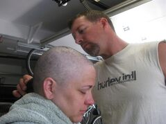 In this August 2012 photo provided by Arrica Wallace, husband Matthew shaves Arrica's head when her hair was falling out in Manhattan, Kan. Arrica Wallace was 35 when her cervical cancer was discovered in 2011. It spread widely, with one tumor so large that it blocked half of her windpipe. The strongest chemotherapy and radiation failed to help, and doctors gave her less than a year to live. But her doctor heard about an immune therapy trial at the Cancer Institute and got her enrolled.