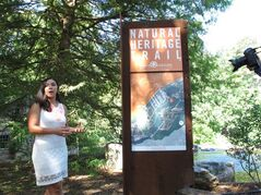 Clemson University student Nicole Nguyen shows off a sign made by her fellow architecture students at the South Carolina Botanical Garden on Wednesday, July 23, 2014, in Clemson, S.C. Clemson students helped rebuild the garden after a July 2013 flood did $225,000 in damage and swept away thousands of plant species. (AP Photo/Jeffrey Collins)