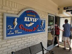 In this photo taken on Tuesday, July 1, 2014, tourist enter the Graceland attraction to an exhibit where two planes once owned by late singer Elvis Presley are displayed in Memphis, Tenn. The company that operates Graceland has told the planes' current owners that it wants them removed from Graceland by late April 2015, or shortly afterward. (AP Photo/Adrian Sainz).