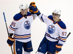 Edmonton Oilers' David Perron, right, celebrates his third goal against the Vancouver Canucks in Vancouver, on Monday January 27, 2014. THE CANADIAN PRESS/Darryl Dyck