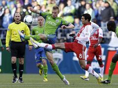 Seattle Sounders' Andy Rose vies for the ball with Portland Timbers' Diego Valeri (8) in the first half of an MLS soccer match, Saturday, March 16, 2013, in Seattle. (AP Photo/Ted S. Warren)