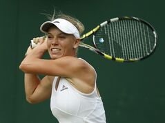 Caroline Wozniacki of Denmark watches a return to Shahar Peer of Israel during their first round match at the All England Lawn Tennis Championships in Wimbledon, London, Monday, June 23, 2014. (AP Photo/Alastair Grant)