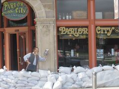 FILE - In this May 31, 2013, file photo, sandbags are piled around the Parlor City Pub and Eatery in Cedar Rapids, Iowa, where workers placed a cardboard cutout of a man drinking beer. Congress is on the cusp of passing its first infrastructure bill of the year. The Senate is expected to vote Thursday, May 22, 2014, on a $12.3 billion water resources bill that authorizes 34 water projects, from managing flood risks in Cedar Rapids, Iowa, and environmental restoration in Louisiana to dredging Boston Harbor. (AP Photo/Ryan J. Foley, File)