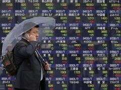 A man talking on a mobile phone walks by the electronic stock board of a securities firm in Tokyo, Wednesday, April 24, 2013. An increase in new U.S. home sales and strong corporate earnings across a range of industries lifted investment sentiment in Asia, where most stock markets rose Wednesday. Japan's Nikkei 225 index jumped 1.8 percent to 13,772.98, trading above 13,700 for the first time in nearly five years. South Korea's Kospi rose 1 percent to 1,936.83. Australia's S&P/ASX 200 added 1.4 percent to 5,087.90. (AP Photo/Itsuo Inouye)