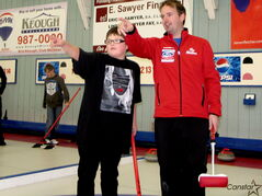 World curling champion Reid Carruthers and George Waters Middle School student Haven Nepinak discuss strategy at the Deer Lodge Curling Club.
