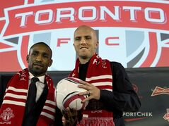 Toronto FC's new players Jermain Defoe and Michael Bradley (righ) pose for a photo at their introductory news conference in Toronto on Monday, January 13, 2014. THE CANADIAN PRESS/Frank Gunn