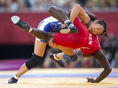 Canada 's Carol Huynh takes down Isabelle Sambou of Senegal to win the Bronze medal match in 48kg Women's Freestyle Wrestling at the Olympic Games in London on Wednesday August 8, 2012. THE CANADIAN PRESS/Frank Gunn