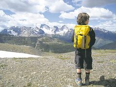 Six-year-old Finn Borstmayer takes in the view after the helicopter drops hiking families off on a snow-touched summit.