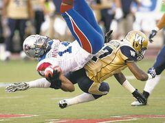 Ryan Remiorz / the canadian press Bombers' Demond Washington upends Alouettes receiver Brandon London in the first quarter Thursday night at Montreal's Percival Molson Stadium.