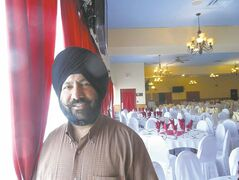 Ravinder Singh Buttar stands in the massive Punjab Banquet Hall.