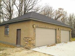 Double garage with stucco finish and stone details.