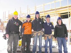 Teacher Larry Schroeder (from left), Philip Blouin, Tanner Koroscil, Dylan Bonchuk and Stewart Salmon pose in front of a home under construction.