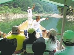 An oarsman piloting an excursion boat down the Hozu River, just outside Kyoto points out sights to his passengers. The two-hour ride down the river offers the chance to spot wildlife while threading rocks and rapids, and is an especially appealing outing for a trip with children.